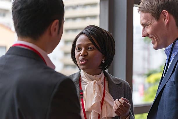 international businesspeople are talking at hallway of office building - translator stock photos and pictures