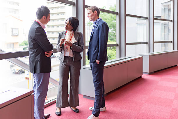 International hommes et femmes d'affaires parlons de couloir d'immeuble de bureaux - Photo