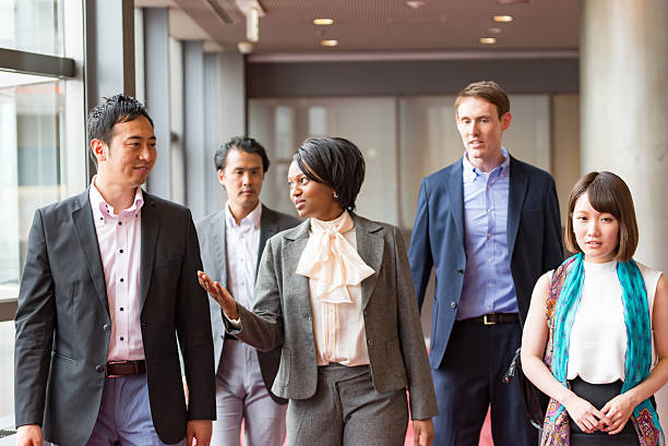 International businesspeople are walking together at hallway of office building International businesspeople are walking together at hallway of office building global village stock pictures, royalty-free photos & images