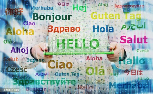 Young woman holding electronic tablet showing the word hello in different languages. Learning and speaking many languages easier using modern technology. International communication concept.