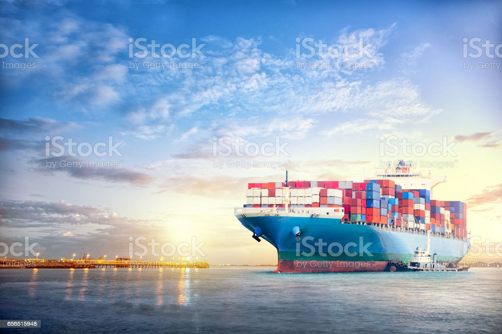 International Container Cargo ship in the ocean at sunset sky, Freight Transportation, Nautical Vessel stock photo