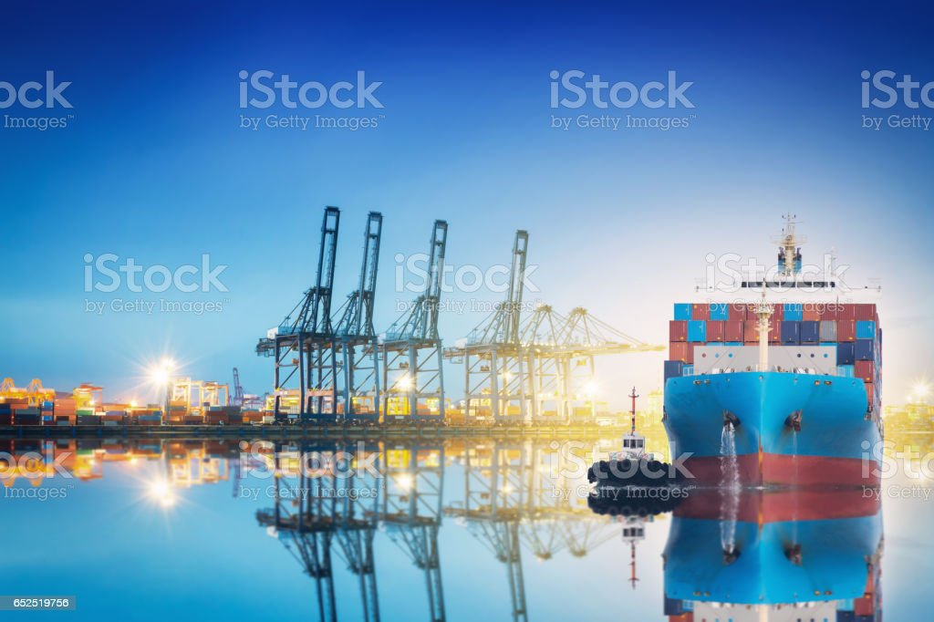 International Container Cargo ship with working crane bridge in shipyard background, logistic import export background and transport industry. stock photo