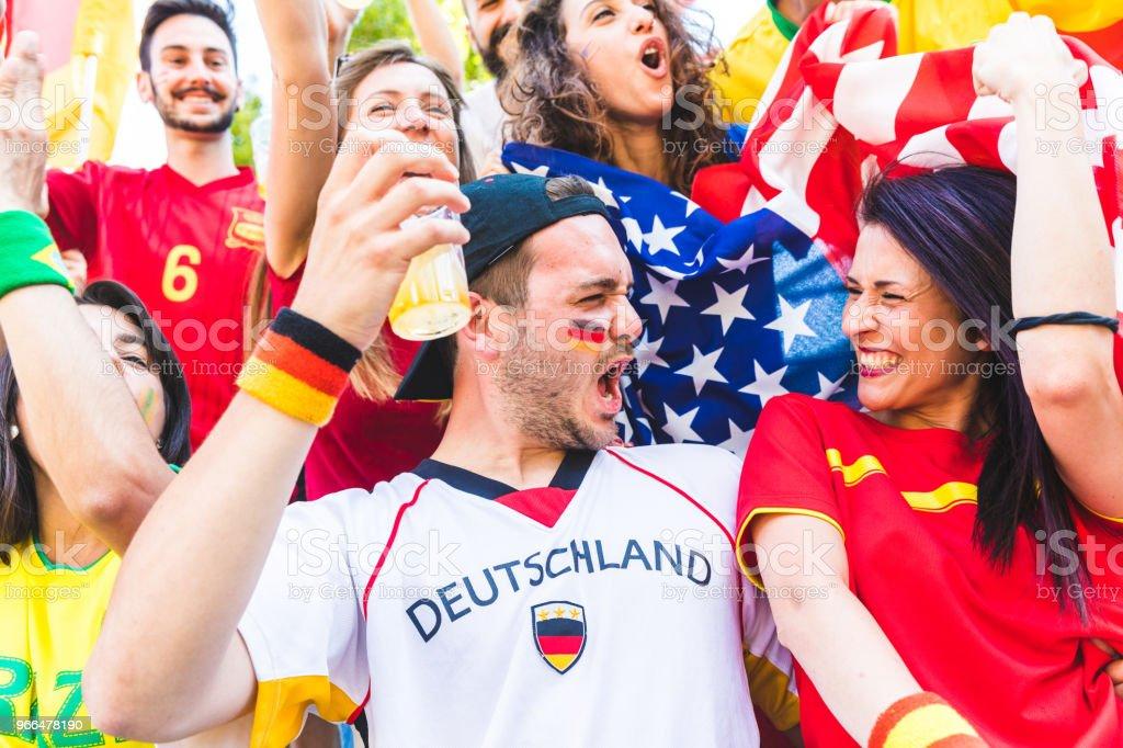 Casal Internacional de fãs comemorando juntos no estádio durante uma partida - foto de acervo