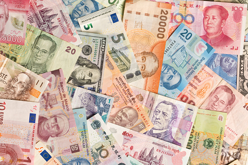 A colorful variation and collection of international currency, a global business money exchange and finance. Photographed in studio, at high angle in horizontal format.