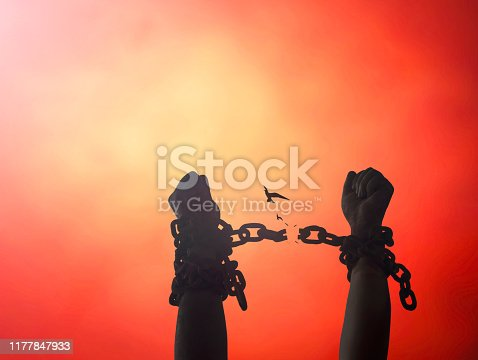 Silhouette human hands raising and broken chains at night background