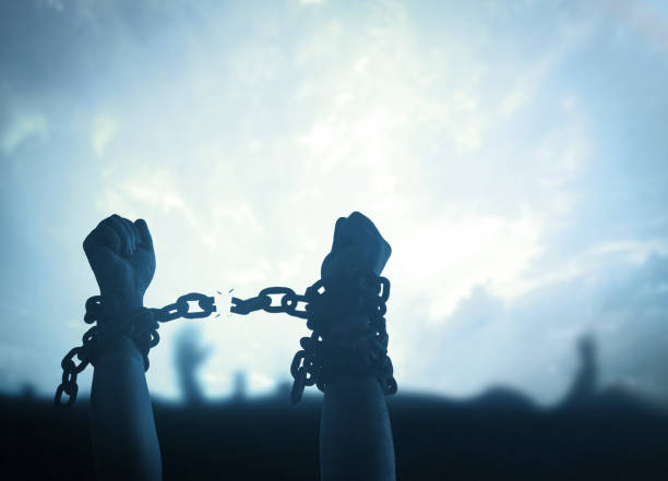 International day for the remembrance of the slave trade and its abolition concept Silhouette human hands raising and broken chains at night background trafficking stock pictures, royalty-free photos & images