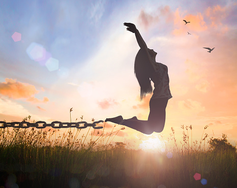 Silhouette of a woman jumping with her hands raised and broken chains at meadow autumn sunset