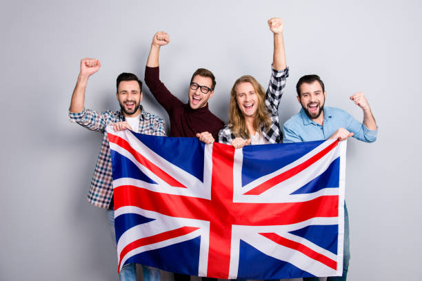 international ethnicity language learn course university concept. friendly excited cheerful guys screaming rejoicing putting fists up triumphing holding jack union flag isolated on gray background - english foto e immagini stock