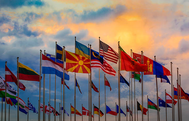 International flags against sunset sky Group of flags of many different nations against sunset sky  national flag stock pictures, royalty-free photos & images