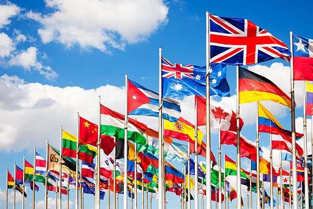 International flags Group of flags of many different nations against blue sky and infront of a convention center. national flag stock pictures, royalty-free photos & images