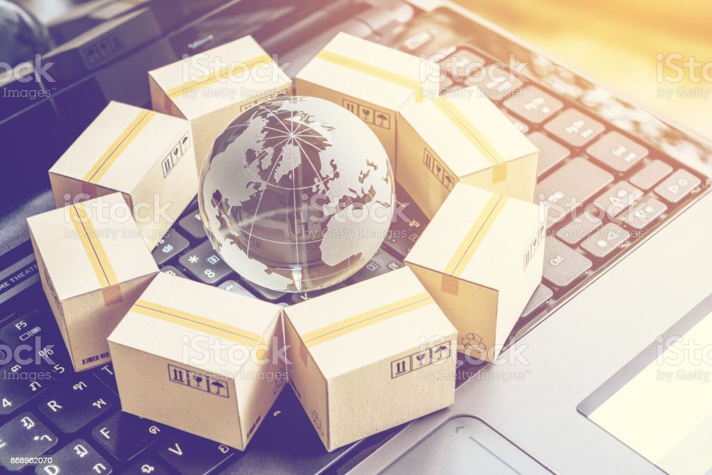 International freight or shipping service for online shopping or ecommerce concept : Paper boxes or carton put in circle around a clear crystal globe with world map on a computer notebook keyboard. stock photo