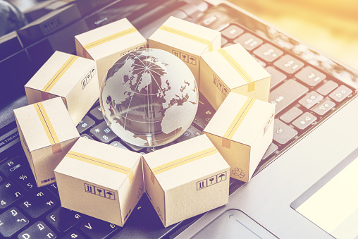 International Freight Or Shipping Service For Online Shopping Or Ecommerce Concept Paper Boxes Or Carton Put In Circle Around A Clear Crystal Globe With World Map On A Computer Notebook Keyboard - Fotografie stock e altre immagini di Accessibilità