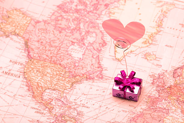 International Gift of Love on Rose Colored Map Bright, shiny symbol of affection gift being sent between Europe and North America long distance relationship stock pictures, royalty-free photos & images