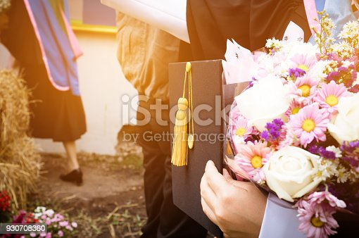959387240 istock photo International graduate study concept : Graduation black cap on students woman hands with flowers on graduation day in university 930708360