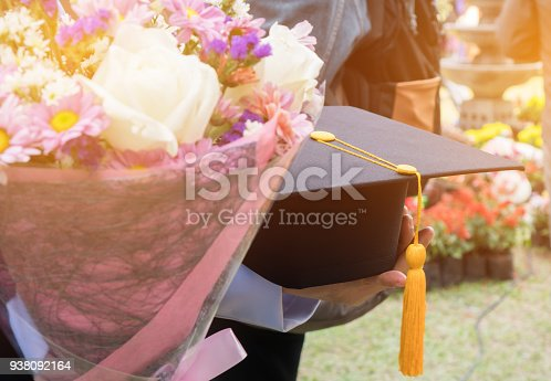 959387240 istock photo International graduate study concept : Graduation black cap on students woman hands with flowers on graduation day in university. Education certificate of Abroad program to success 938092164