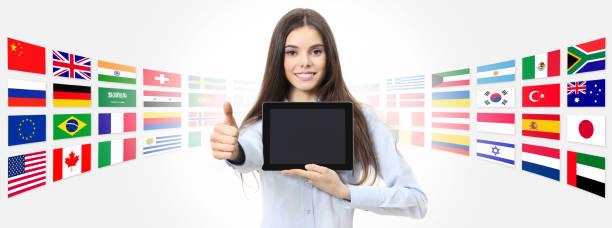 internationale sprache schule konzept lächelnde frau mit wie daumen zeigt digital-tablette auf globalen flags hintergrund - online lexikon stock-fotos und bilder