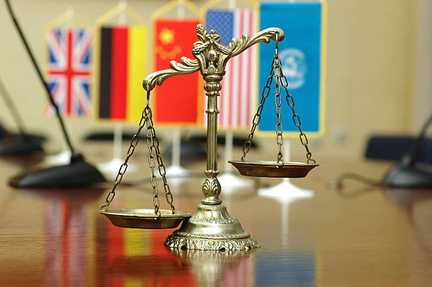 International law and order Decorative Scales of Justice with blurred National flag of different countries, concept of International Law and Order, focus on the scales global village stock pictures, royalty-free photos & images