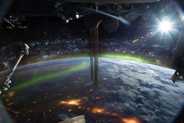 International space station on orbit of Earth planet. ISS. Stars and galaxies, city lights and aurora polaris, lens flare and clouds. Elements of this image furnished by NASA.