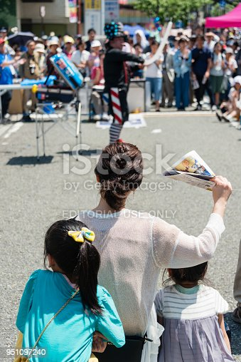 Yokohama, Japan - April 22, 2018: People are looking at a balloon artist on the Noge street in the International Street Performers Festival, which takes place on April 21 through 22 in 2018 in Yokohama, Japan. The performer is making a balloon art.