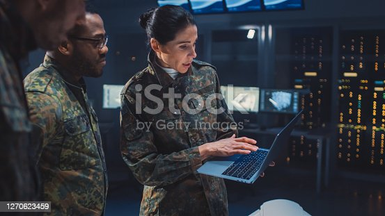 International Team of Military Personnel Have Meeting in Top Secret Facility, Female Leader Holds Laptop Computer Talks with Male Specialist. People in Uniform on Strategic Army Meeting