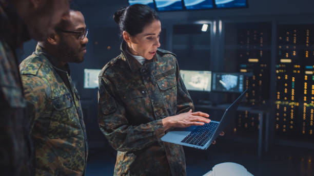 International Team of Military Personnel Have Meeting in Top Secret Facility, Female Leader Holds Laptop Computer Talks with Male Specialist. People in Uniform on Strategic Army Meeting International Team of Military Personnel Have Meeting in Top Secret Facility, Female Leader Holds Laptop Computer Talks with Male Specialist. People in Uniform on Strategic Army Meeting military stock pictures, royalty-free photos & images