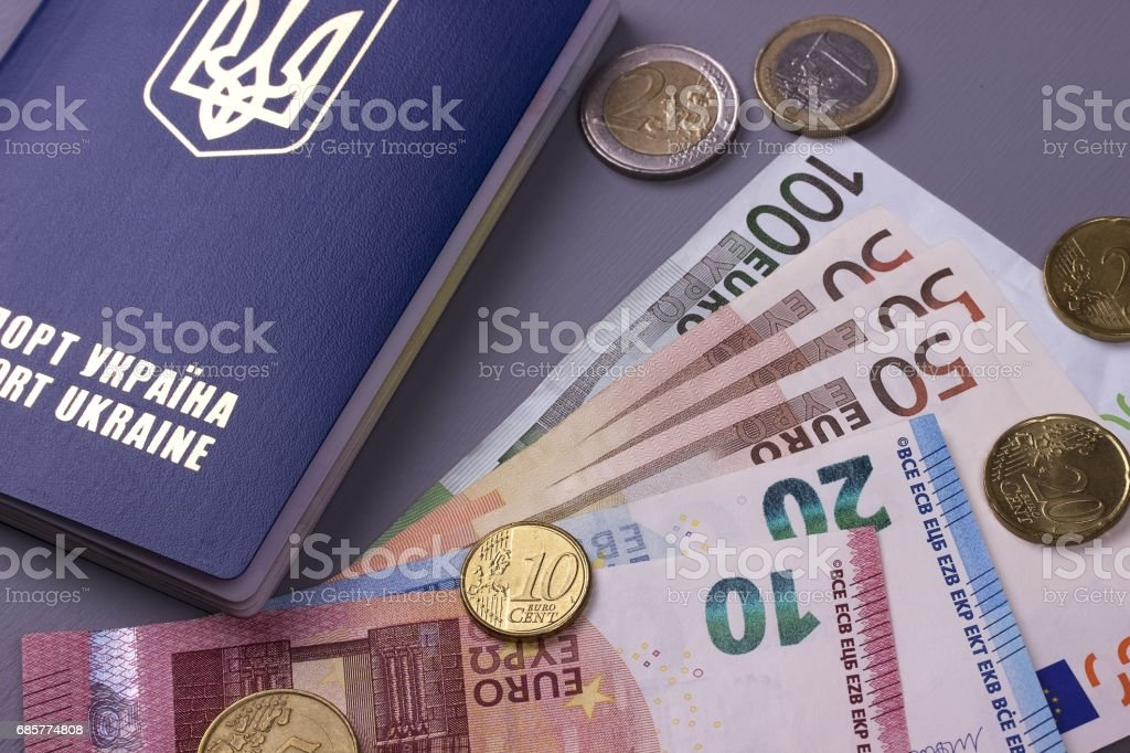 International Ukrainian passport with Euro banknotes isolated on gray background. royalty-free stock photo
