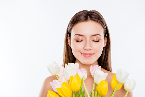 International women's day, wellbeing concept. Close up portrait of tender gentle woman with pure flawless face skin smelling aroma of tulips with close eyes isolated on white background