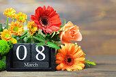International Womens Day. Wooden calendar and bunch of flowers