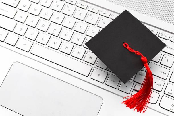 Aprendizaje académico en Internet, e-learning y la educación universitaria en línea tema conceptual con cerca de la gorra de graduación con borla roja en el teclado de la computadora con Copyspace - foto de stock