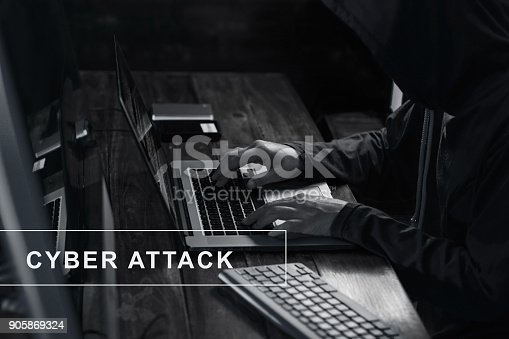 istock Internet crime. Hacker using laptop and hack code password in the dark room. Cyber attack concept 905869324