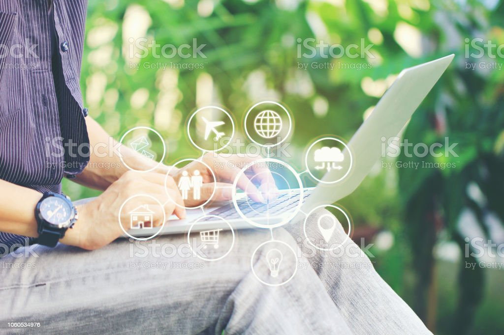 Internet of Things (IoT), Business man using laptop computer and iot icon or hologram with in home office, Communication network service and Business concep stock photo