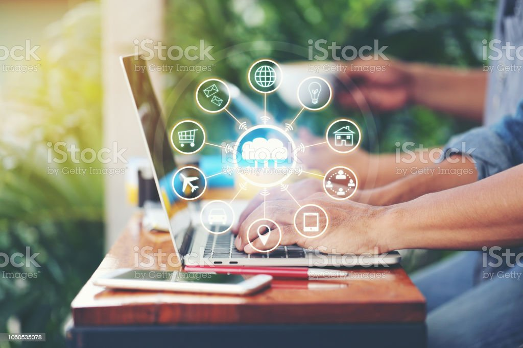 Internet of Things (IoT), Business man using laptop computer and iot icon or hologram with in coffee shop, Communication network service and Business concept stock photo