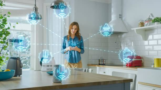 Internet of Things Concept: Young Woman Using Smartphone in Kitchen. She controls her Kitchen Appliances with IOT. Graphics Showing Digitalization Visualization of Connected Home Electronics Devices stock photo