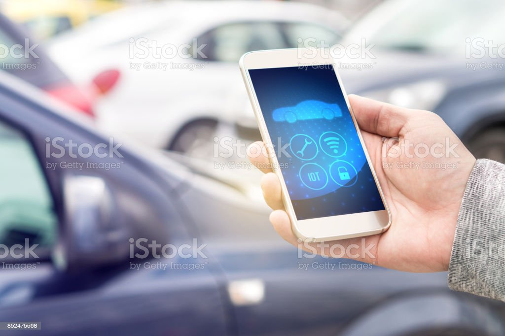Internet of things (IOT) mobile app in smart phone for modern car. Hand holding smartphone controlling ADAS system. Vehicles parked in the background. stock photo