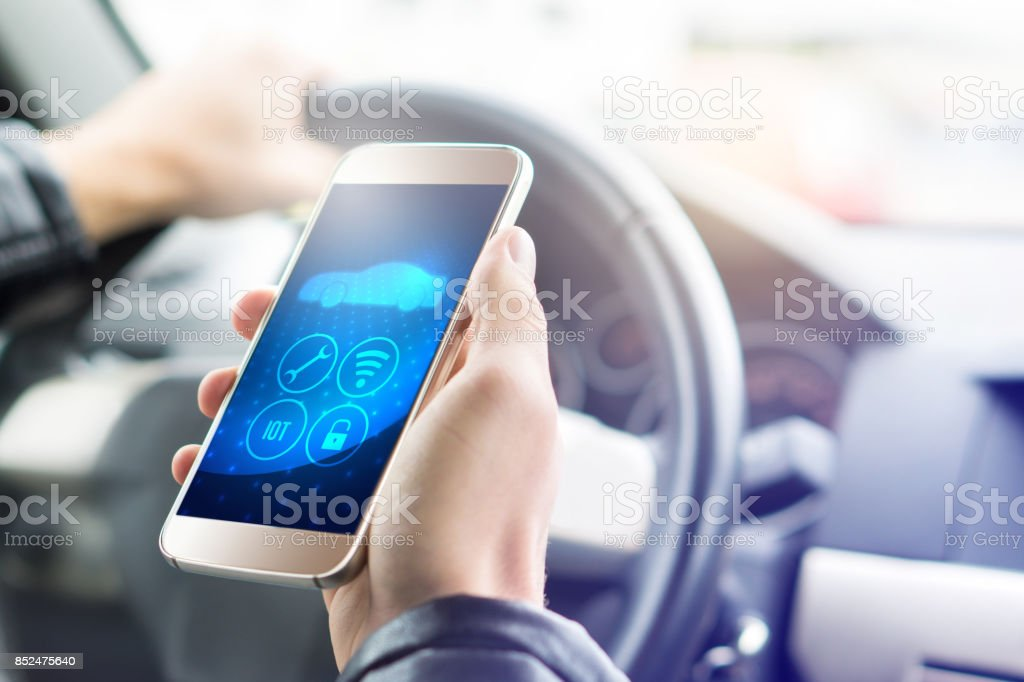 Internet of things (IOT) mobile app in smart phone for modern car. Hand holding smartphone with futuristic ADAS system. Vehicle with autonomous self control. Interior view in cockpit. stock photo