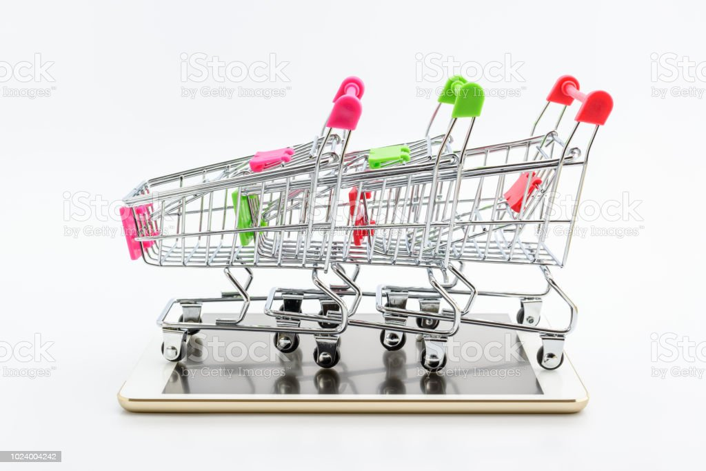 d349f575776 Internet online shopping and delivery service concept   Three colors  shopping carts on a white smart mobile tablet. Contemporary buyers always  shop products ...