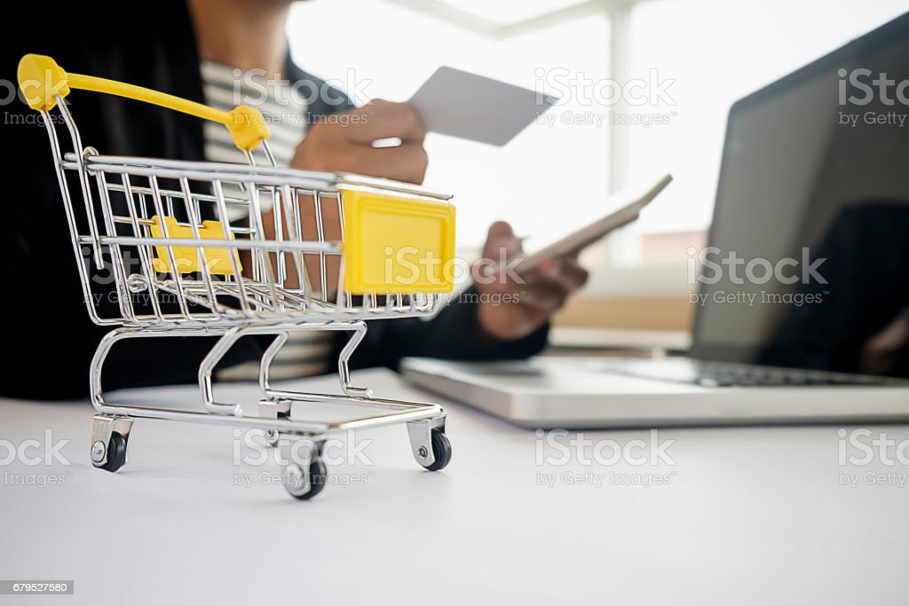 Internet online shopping concept with laptop and shopping-cart.Vintage tone retro filter effect,soft focus(selective focus) royalty-free stock photo