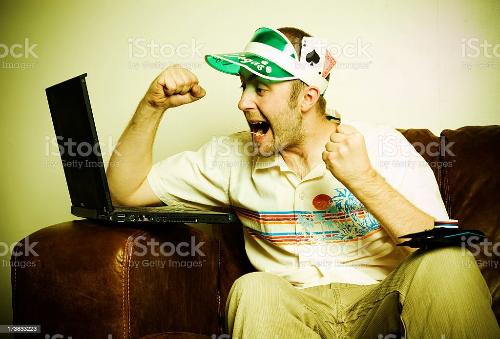 Internet poker player with visor cheering at laptop stock photo