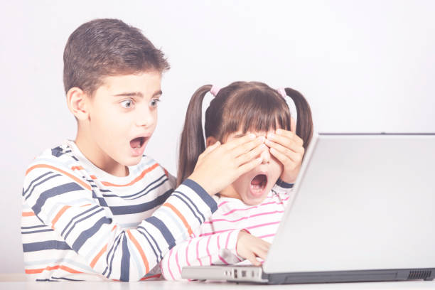 Internet safety for kids concept Little boy protects his sister from watching inappropriate content while using a computer shock tactics stock pictures, royalty-free photos & images