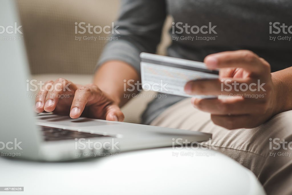 Internet shopper entering credit card information using laptop keyboard stock photo