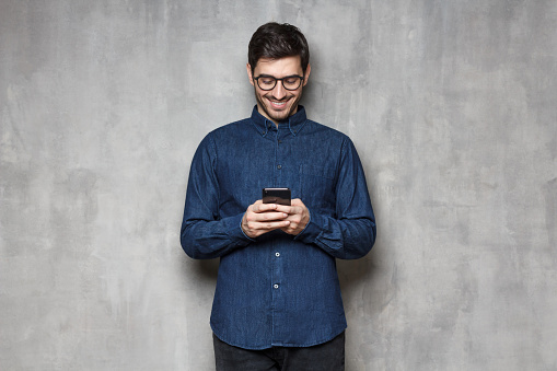 825083556 istock photo Internet surfing using smartphone. Portrait of young smiling man typing a message with new app on his phone, standing against gray textured wall 1164586372