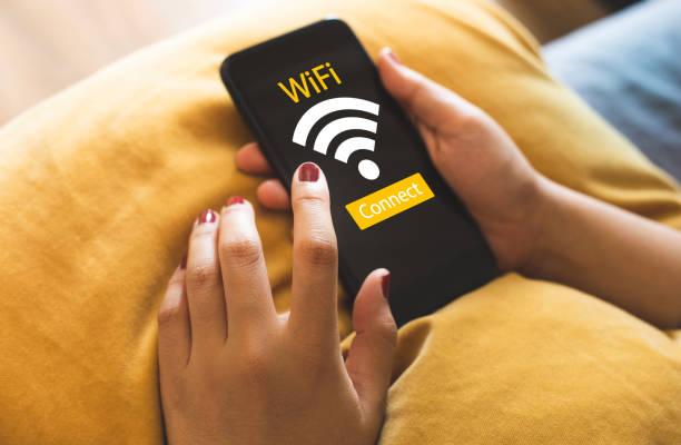internet-wlan-konzepte mit nahestehenden jungen frauen mit smartphone auf dem sofa. technologie-kommunikation - iphone gratis stock-fotos und bilder