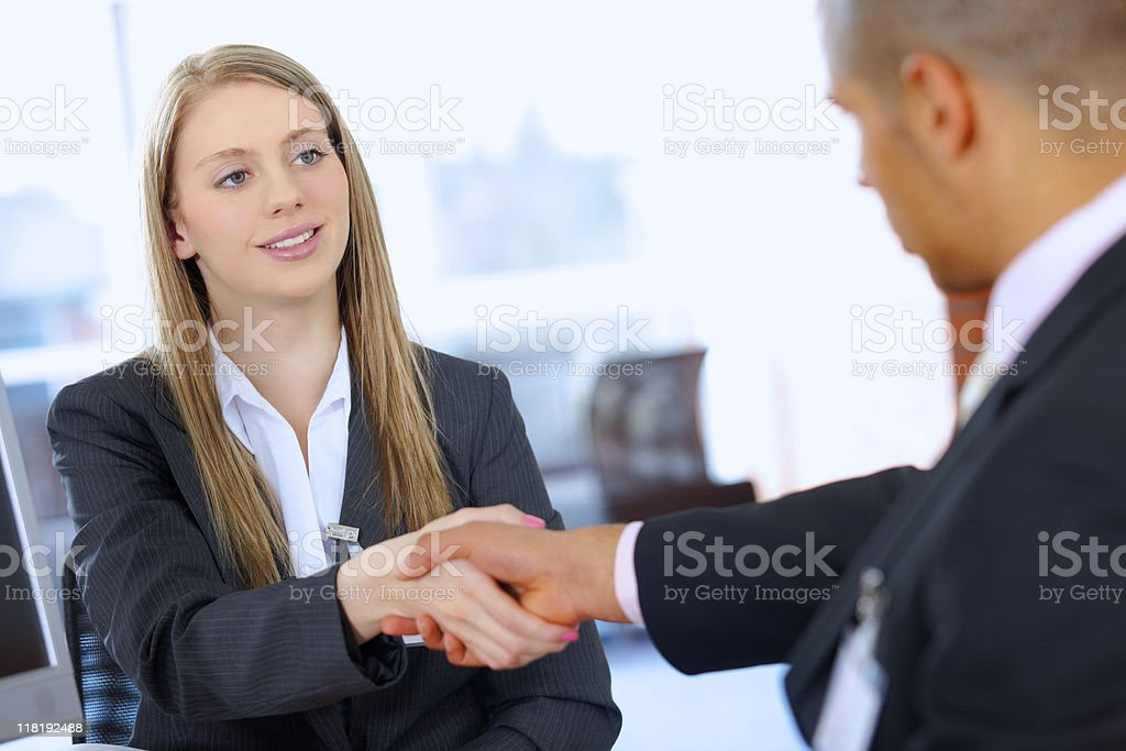 interracial Business couple shaking hands in modern office royalty-free stock photo