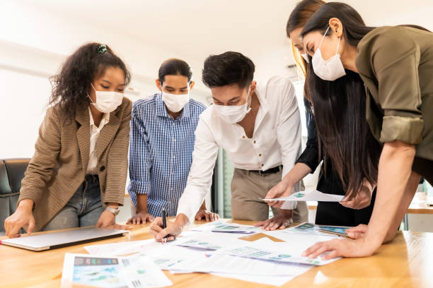 Interracial business team wear face mask brainstorm at new normal office stock photo