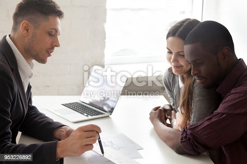 1040654052 istock photo Interracial couple considering mortgage or buying house consulting with realtor 953226892
