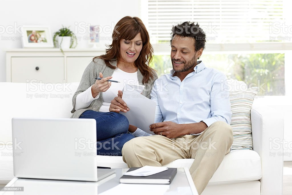 Interracial couple dealing with home finances stock photo