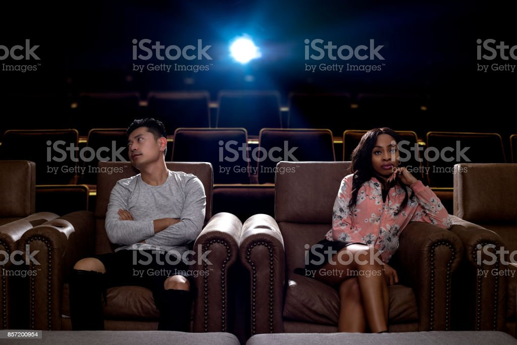 Interracial Couple Fighting in a Movie Theater stock photo