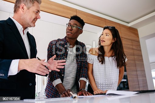 istock Interracial couple having consultation with a realtor 902167334