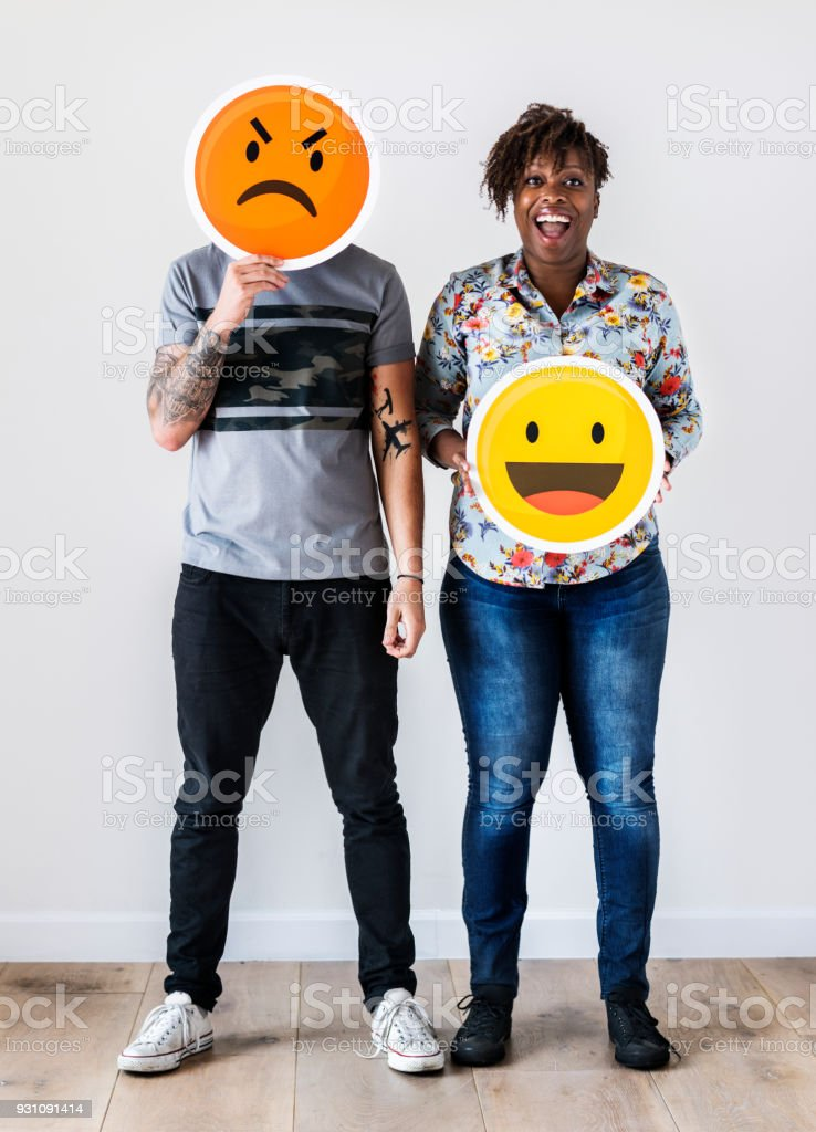 Interracial couple holding an expressive emoticon face facial expression frown and smile relationship issue concept stock photo