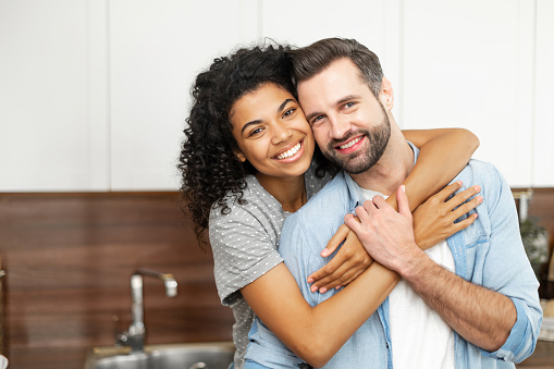 Close-up of happy interracial couple posing over blurred kitchen background, happy owners of new flat smiling and looking at the camera, young African American woman hugging handsome man from behind